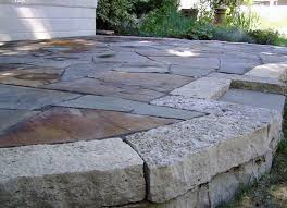diy raised flagstone patio with concrete block border next to house