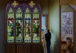andrew mann takes a quick measurement of the stained glass series he donated to st timothy