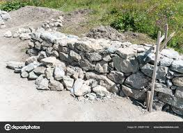 traditional rock wall construction site wooden frame swiss alps stock photo