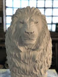 large garden sculpture of a sitting lion on a stand white