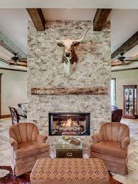 example of a mountain style living room design in houston with a two sided fireplace