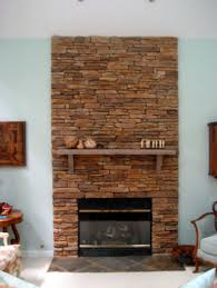 make over fireplace with stacked red stone fireplace veneer with gas fireplace with glass fireplace screen and wooden fireplace mantel shelf