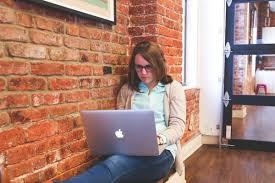 how to write a job description in 4 fast steps hiring manager at a startup writing a job description on her laptop