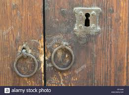 two rusty iron ring door s and keyhole over an old wooden grunge door
