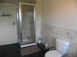 contemporary style bathroom ideas with white toilet seat and chrome frame glass shower enclosure on black ceramic floor also fur floor door mat plus white
