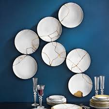 Table plates hanged as a decoration , Kintsugi techique with gold  Fascinating home decoration Blue wall