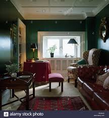 Wing chair and brown leather sofa in dark green living room with antique  tray table and table with red cloth