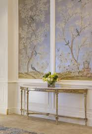 An elongated demilune gilded table is balanced by the soft sheen of  shimmering blue panels,. Wallpaper ...