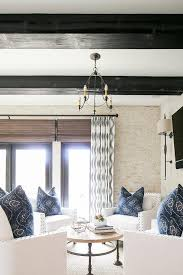 an iron chandelier hangs from a ceiling accented with black ceiling beams over a round industrial coffee table placed on a seagrass rug and surrounded by