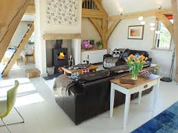eco living on a budget living room with oak frame sling brace truss and woodburner in self build timber house in
