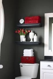floating shelves were installed over the toilet for additional storage filled with bathroom necessities and