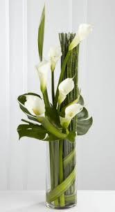 Eternal friendship vase arrangement - a stylized vase arrangement of white  calla lilies and assorted foliages