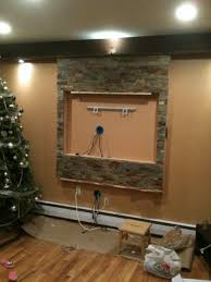 TV wall mount and entertainment center, Wall framed and covered in natural  stone for my massive 55 inch HDTV, the natural stone being attach.
