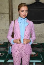 Bel Powley wearing a pink lace suit and pale blue pussy bow blouse.