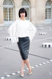 stock photo woman with brunette hair in black leather skirt white blouse pose in courtyard of paris france lifestyle vacation travelling