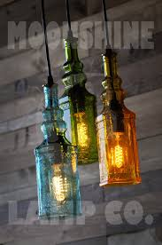 This chandelier is made from three repurposed colored square bottles. The  bottles can be all the same color, or a variety, as pictured.