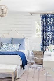 white and blue bedroom boasts shiplap walls lined with a white grid nailhead headboard on bed