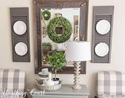 this modern farmhouse living room features a beautiful brass framed mirror between repurposed shutters and white dinnerware