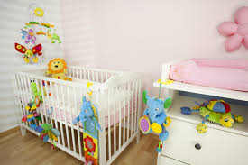 Playful Baby Girl Nursery Designing With White Wooden Crib Baby Corner And  Many Doll In The