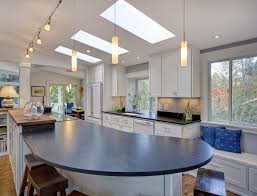 kitchen track lighting and pendant lamps over kitchen island also skylight on vaulted ceiling
