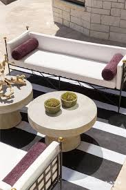 adorned with purple bolster pillows facing each other across from side by side round stone cocktail table atop a black and white striped outdoor rug