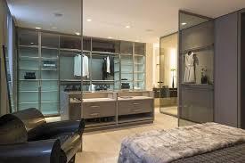 decoração para quarto com closet e banheiro com poltrona moderna e portas de vidro foto joão