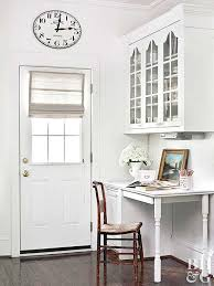 built in kitchen desk by entry way glass door storage cabinets above desk