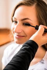 makeup artist applying mascara on happy woman s face free photo