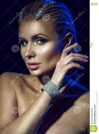 portrait of gorgeous glam woman with wet hair decorated with str artistic glittering make up and shoulders holding a hand in jewel bangle close to