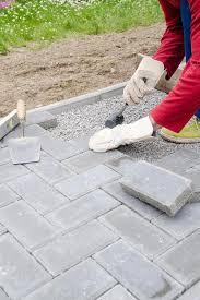 bricklayer places concrete paving stone