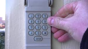 a hand punches a number on a beige garage door keypad mounted on the siding near