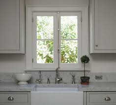 tone on tone beautiful kitchen with light gray shaker kitchen cabinets white carrara marble countertops farmhouse sink french windows and topiary