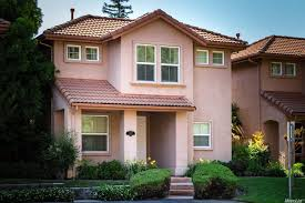 deep red clay tiles on a home with stucco siding is what normally comes to mind when we picture roof