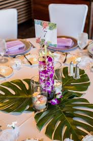 One of our tropical centerpieces with monstera leaves. The other tables  alternated between monstera and