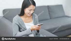 woman play mobile game on cellphone at home photo by leungchopan