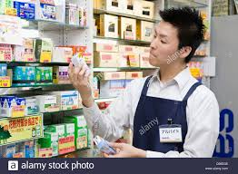 clerk of drugstore holding and looking merchandise stock photo clerk of drugstore holding and looking merchandise