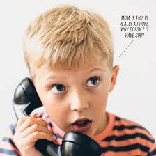 school aged boy talking on the phone with a surprised look on his face