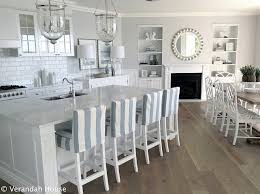 white on white coastal kitchen with blue and white striped barstools