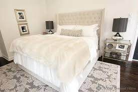 bedroom with beige tufted headboard accented with soft white bedding zebra lumbar pillow and ivory faux fur throw blanket over white and gray rug ivory
