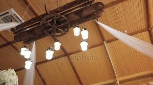 rustic chandelier on the high ceiling in a wooden house hall decorated with flowers to