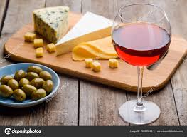 set of wine and appetizers a light blue plate of fresh olives various types of cheese on cutting board and a glass of red wine on wooden table