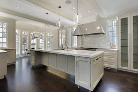 modern white cabinet kitchen with beautiful light fixtures pendant lights and dark wood floors
