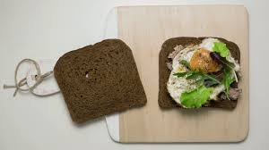 A Sandwich With Canned Fish And Scrambled Eggs And A Mix Of Salad On