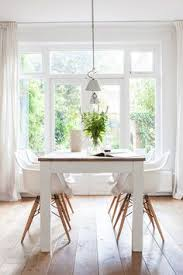 clean pretty white dining room but diffe chairs