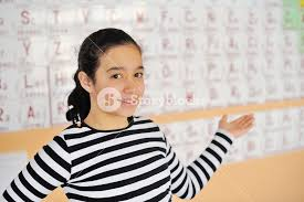 Beautiful girl standing in front of a periodic table of elements ...