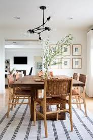 modern dining room with wood table black chandelier and woven leather dining chairs jdpinteriors