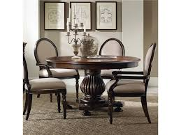 round dark brown wooden round dining room table with pedestal added by four black wooden chairs on the rug