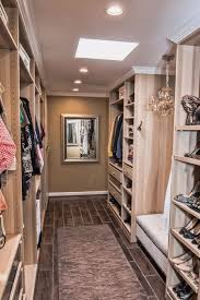 galley style walk in closet with wood grain floor tiles and small chandelier