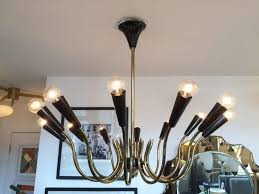 imposing 12 arm 12 light chandelier with curved brass arms black enameled