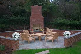 distinctive backyard brick fireplaces design with modern outdoor wooden table and chairs with beautiful green field